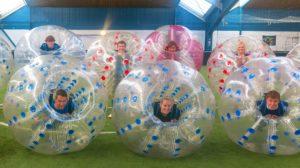 Junge Menschen liegen in Bubbleballs und haben Spaß.