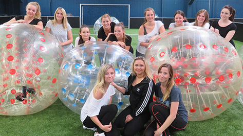 Eine Gruppe junger Frauen steht mit drei großen Bubbleballs auf einem Fußballfeld.