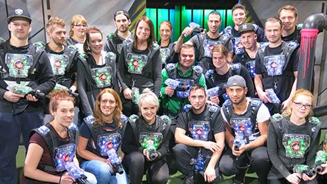 Eine große Gruppe mit Lasertag-Kleidung lächelt in die Kamera und hat Spaß.
