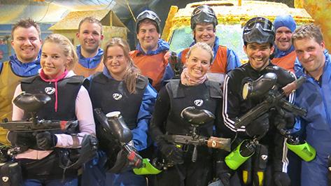 Eine Gruppe hält Paintball Markierer in der Hand und lächelt.