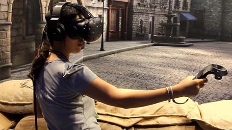 Eine junge Frau trägt eine VR-Brille und bewegt sich vor einer großen Stadtkulisse.