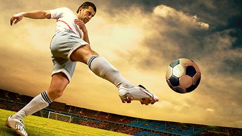 Ein Fußballer schießt einen Ball durch ein Stadion.